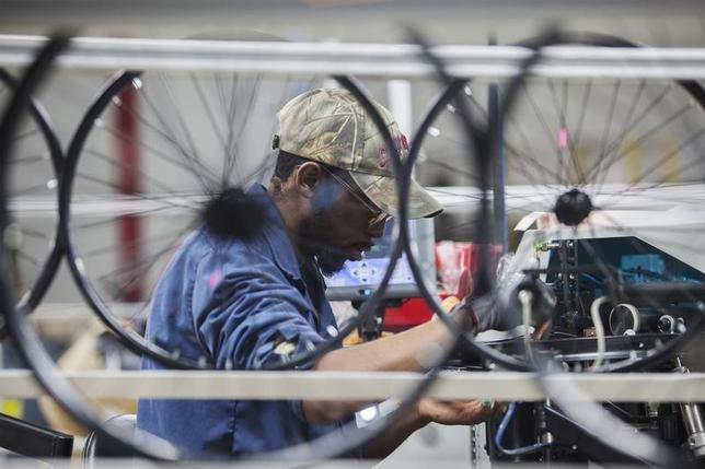 Employee Edward Klutz operates a wheel lacing machine at the new Bicycle Corporation of America plant in Manning, South Carolina, November 19, 2014.  REUTERS/Randall Hill