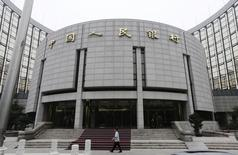 Una persona camina frente a la sede del Banco Popular de China, en Pekín, 25 de junio de 2013. Un alza general de los niveles de deuda en China está aumentando los riesgos financieros, dijo el viernes el banco central del país en su informe de política monetaria del segundo trimestre, publicado online. REUTERS/Jason Lee