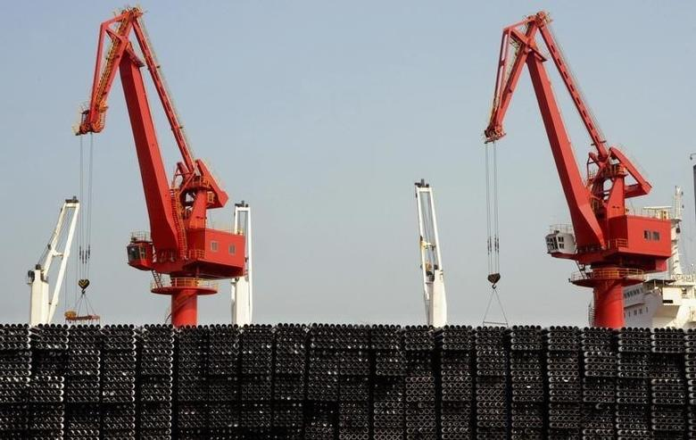 Piles of steel pipes to be exported are seen in front of cranes at a port in Lianyungang, Jiangsu province March 7, 2015.  REUTERS/Stringer