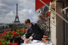 An employee prepares breakfast in front of the Eiffel tower at the Parisian luxury hotel Le Plaza Athenee, France July 30, 2015. Nowhere in the world has more accommodation available on Airbnb than Paris. Now the home-sharing website that has transformed budget travel to the French capital is giving its super-deluxe hotels a fright too. Picture taken France July 30, 2015. REUTERS/Stephane Mahe