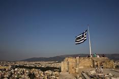 Una bandera de Grecia flameando en la Acrópolis en Atenas, jul 26 2015. El Fondo Monetario Internacional (FMI) cree que los prestamistas internacionales de Grecia tendrán que aumentar el tamaño de un tercer rescate a 90.000 millones de euros (98.900 millones de dólares), informó el lunes el diario alemán Handelsblatt.  REUTERS/Ronen Zvulun
