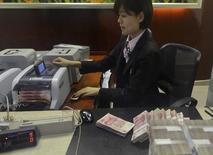 Funcionária conta notas de 100 iuanes em agência bancária na China. 20/04/2015 REUTERS/Stringer
