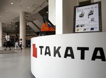 Visitors walk behind a logo of Takata Corp on its display at a showroom for vehicles in Tokyo, Japan, June 25, 2015. REUTERS/Yuya Shino