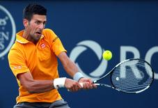 Aug 11, 2015; Montreal, Quebec, Canada; Novak Djokovic of Serbia hits a shot against  Thomaz Bellucci of Brazil (not pictured) during the Rogers Cup tennis tournament at Uniprix Stadium. Jean-Yves Ahern-USA TODAY Sports