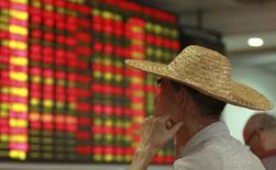 Homem olhando painel de cotações da bolsa de valores em Haikou, na China.  11/08/2015    REUTERS/Stringer