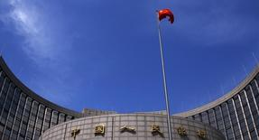 Una bandera de China ondea frente al Banco Popular de China, en Beijing, 16 de mayo de 2014.  Las bolsas de Asia y las materias primas caían el miércoles luego de que China permitió que el yuan se depreciara bruscamente por segundo día consecutivo, lo que obligó a los inversores a buscar refugio. REUTERS/Petar Kujundzic