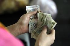 Una persona cuenta yuanes en un mercado en notes Pekín, ago 12 2015. El yuan chino retrocedió el miércoles a un mínimo de cuatro años, en su segunda sesión consecutiva de pérdidas, luego que las autoridades devaluaron a la moneda, una decisión que avivó el temor a una guerra mundial de divisas y levantó críticas contra Pekín por ofrecer una ventaja injusta a sus exportadores.  REUTERS/Jason Lee