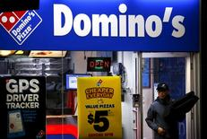 A worker carries a pizza for delivery as he exits a Domino's pizza store in Sydney, Australia, August 12, 2015.  REUTERS/David Gray