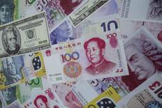 Рекламный щит с изображениями банкнот у пункта обмена валюты в Гонконге. 13 августа 2015 года. Для дальнейшего падения юаня больше нет оснований, учитывая сильные экономические показатели страны, заявил в четверг Центрбанк Китая в попытке успокоить мировые рынки после неожиданно девальвации валюты на этой неделе. REUTERS/Tyrone Siu