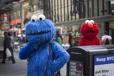 Characters dressed up as the Cookie Monster and Elmo from Sesame Street stand in Times Square while waiting to pose for photographs with people for tips in New York April 9, 2013. REUTERS/Shannon Stapleton