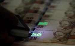 Un trabajador revisa plantillas de billetes de 50 reales en la Casa de la Moneda de Brasil en Río de Janeiro, ago 23 2102. El real brasileño se negocia en su valor justo o casi en ese nivel después de caer un 25 por ciento contra el dólar desde el 1 de enero, dijeron economistas, sugiriendo un posible alivio para una de las monedas más golpeadas del año.  REUTERS/Sergio Moraes