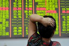 An investor looks at an electronic board showing stock information at a brokerage house in Hangzhou, Zhejiang province, China August 18, 2015. REUTERS/China Daily