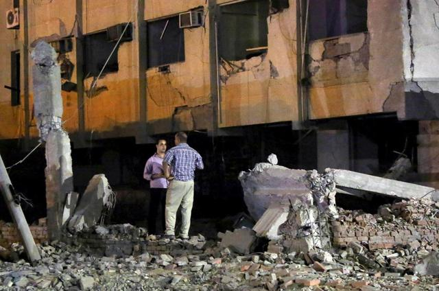 Security officials stand at the site of a bomb blast at a national security building in Shubra Al-Khaima on the outskirts of Cairo, Egypt August 20, 2015.  REUTERS/Mohamed Abd El Ghany