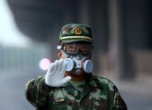 Член военизированного формирования в Тяньцзине 17 августа 2015 года. Уровень цианида у китайского порта Тяньцзинь, серьезно пострадавшего после серии мощных взрывов на прошлой неделе, в 277 раз превышает норму, сообщили власти КНР, отметив, что питьевой воды загрязнение не коснулось. REUTERS/Kim Kyung-Hoon