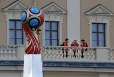 Volunteers take pictures of the 2018 World Cup logo at the Konstantin (Konstantinovsky) Palace in St. Petersburg, July 24, 2015.  REUTERS/Maxim Shemetov