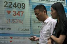 """Transehúntes pasan frente a pizarra que marca el cierre del Índice Hang Seng fuera de un banco en Hong Kong, China , el 21 de agosto de 2015. La desaceleración económica de China y la fuerte caída de su mercado accionario no es el anuncio de una crisis sino un ajuste """"necesario"""" de la segunda economía del mundo, dijo el sábado un alto funcionario del Fondo Monetario Internacional (FMI). REUTERS/Tyrone Siu"""