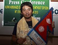 Japanese climber Kuriki Nobukazu holds a flag of Nepal during an announcement of his solo expedition of Mount Everest in Kathmandu August 20, 2010. REUTERS/Gopal Chitrakar