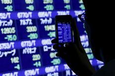 Un hombre toma fotografías de los índices de mercado afuera de una correduría en Tokio, 24 de agosto de 2015. Las acciones asiáticas y el petróleo caían el lunes, en otro duro revés para los mercados, debido a la creciente preocupación entre los inversores de que la desaceleración de la economía china siga castigando a las bolsas. REUTERS/Thomas Peter
