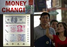 Люди у пункта обмена валюты в Сингапуре. 24 августа 2015 года. Курс доллара растет к евро и иене после снижения процентных ставок в Китае, которое остановило падение китайского фондового рынка. REUTERS/Edgar Su