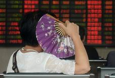 Investidora observa painel eletrônico com informações sobre ações em corretora em Xangai. 26/08/2015  REUTERS/China Daily