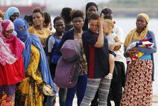 """Мигранты в порту Аугусты, Сицилия 25 августа 2015 года. Десятки несогласных встретили плакатами с надписью """"Предатель!"""" канцлера Германии Ангелу Меркель, которая вступилась за ставших жертвами насилия беженцев, чей растущий поток породил самый масштабный кризис такого рода в Европе со времен Второй мировой. REUTERS/Antonio Parrinello"""