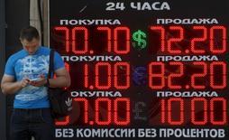 Мужчина у табло обменного пункта в Москве 24 августа 2015 года. Российские денежные власти пообещали не ослаблять усилий в борьбе с инфляцией и ожидают разворота тенденции падения курса рубля, зависимого от цен нефти. REUTERS/Sergei Karpukhin