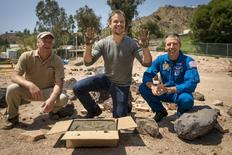 "Actor Matt Damon (C) who stars as NASA Astronaut Mark Watney in the film ""The Martian,"" smiles after having made his hand prints in cement at the Jet Propulsion Laboratory (JPL) Mars Yard, while Mars Science Lab Project Manager Jim Erickson (L), and NASA Astronaut Drew Feustel look on in Pasadena, California in this August 18, 2015 handout photo. REUTERS/Bill Ingalls/NASA/Handout"