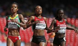 Genzebe Dibaba of Ethiopia (L) crosses the finish line as she wins the women's 5,000 meters heats ahead of Mercy Cherono of Kenya (C) during the 15th IAAF World Championships at the National Stadium in Beijing, China August 27, 2015. REUTERS/Lucy Nicholson