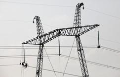 Механики ремонтируют ЛЭП у села Соленоозерное в Хакасии. 1 июля 2012 года. Слабый рубль и запуск новых электростанций в конце прошлого - в первой половине этого года продолжают поддерживать российский энергохолдинг ИнтерРАО, прибыль которого выросла втрое в январе-июне. REUTERS/Ilya Naymushin