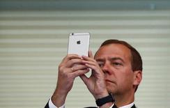Премьер-министр России Дмитрий Медведев с iPhone на чемпионате мира по водным вида спорта в Казани. 9 августа 2015 года. Apple Inc в четверг разослала журналистам приглашения на мероприятие 9 сентября, на котором ожидается презентация новых моделей iPhone. REUTERS/Hannibal Hanschke