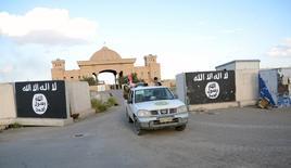 Paramilitares chiíes pasan junto a una muralla pintada con una bandera del Estado Islámico en lo que fuera un palacio de Saddam Hussein en Tikrit, mar 31 2015. Un adolescente de Virginia que usó redes sociales para respaldar al grupo militante Estado Islámico fue sentenciado el viernes a poco más de 11 años en una prisión federal, informó el Departamento de Justicia de Estados Unidos.  REUTERS/Stringer
