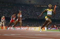 Shelly-Ann Fraser-Pryce of Jamaica (R) crosses the finish line ahead of Jasmine Todd of the U.S. (2nd R) to win the women's 4 x 100 metres relay final during the 15th IAAF World Championships at the National Stadium in Beijing, China, August 29, 2015. REUTERS/Kai Pfaffenbach