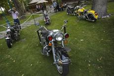 An Iranian visitor takes photograph of Harley Davidson motorcycles during the Tehran Classic Car Show 09 at Niavaran palace in northern Tehran July 21, 2009. REUTERS/Morteza Nikoubazl/Files