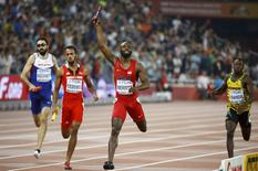 LaShawn Merritt of the U.S. (C) crosses the finish line first to win the men's 4 x 400 metres relay final during the 15th IAAF Championships at the National Stadium in Beijing, China, August 30, 2015.  REUTERS/Damir Sagolj