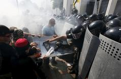 Demonstrators, who are against a constitutional amendment on decentralization, clash with police outside the parliament building in Kiev, Ukraine, August 31, 2015. Several police and members of the Ukrainian national guard were injured on Monday when a grenade was thrown from a crowd of nationalist protesters demonstrating outside parliament in Kiev against a draft law to give special status to separatist regions, police said.   REUTERS/Valentyn Ogirenko