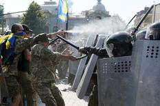 Demonstrators, who are against a constitutional amendment on decentralization, clash with police outside the parliament building in Kiev, Ukraine, August 31, 2015. Several police and members of the Ukrainian national guard were injured on Monday when a grenade was thrown from a crowd of nationalist protesters demonstrating outside parliament in Kiev against a draft law to give special status to separatist regions, police said.  REUTERS/Valentyn Ogirenko      TPX IMAGES OF THE DAY