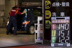 An attendant cleans the window of a car near a sign displaying the petrol station's current fuel prices in yen in Tokyo August 24, 2015. REUTERS/Thomas Peter