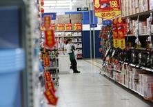 En la imagen, una promotora de ventas espera a clientes en una tienda por departamento en Pekín. 19 de enero, 2015.  El crecimiento del sector de servicios en China se desaceleró en agosto frente al mes anterior, según un sondeo oficial publicado el martes, lo que avivaba el temor a que la segunda mayor economía del mundo se esté enfrentando a un enfriamiento económico mayor al que se esperaba. REUTERS/Kim Kyung-Hoon
