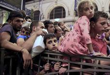 Мигранты пытаются сесть на поезд в Будапеште. 31 августа 2015 года. Поезда, заполненные мигрантами, в понедельник прибыли в Австрию и Германию, поскольку правила ЕС о предоставлении убежища не выдерживают беспрецедентного наплыва беженцев. REUTERS/Bernadett Szabo