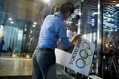 Funcionário retirando placa com logo da Olimpíada de Tóquio de prédio do governo, em Tóquio. 01/09/2015   REUTERS/Thomas Peter