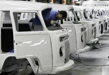 Empleados trabajan en la línea de ensamblaje de Volkswagen, en una planta de la compañía en Sao Bernardo do Campo, 9 de diciembre de 2013. La actividad manufacturera de Brasil se contrajo en agosto por séptimo mes consecutivo, mostró un sondeo privado el martes, debido a que una fuerte caída de nuevos pedidos provocó recortes de puestos de trabajo en medio de un empeoramiento de la recesión económica. REUTERS/Paulo Whitaker