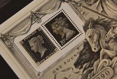 A commemorative stamp (R) from 1990 with depictions of Britain's Queen Elizabeth (R) and Queen Victoria (L) is seen next to an 1840 Penny Black stamp with Queen Victoria on it at Stanley Gibbons in central London, Britain, August 21, 2015.  REUTERS/Toby Melville