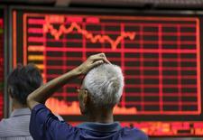 Un inversor mira un tablero electrónico en una correduría en Beijing, 27 de agosto de 2015. Las investigaciones de las autoridades chinas sobre las bruscas oscilaciones del mercado bursátil están generando temor entre los inversores en el país, y algunos no están seguros respecto a si simplemente están colaborando con la pesquisa o si son vistos como sospechosos, dijeron ejecutivos de la comunidad financiera. REUTERS/Jason Lee