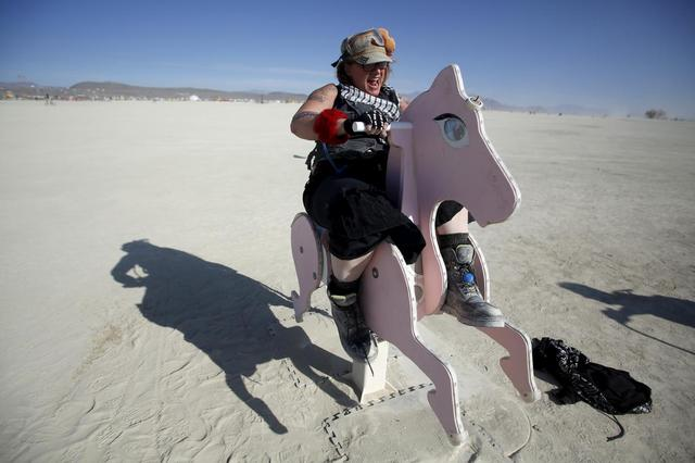 Kentucky Sunshine, her Playa name, rides a rocking horse art installation during the Burning Man 2015 ''Carnival of Mirrors'' arts and music festival in the Black Rock Desert of Nevada, September 1, 2015. REUTERS/Jim Urquhart