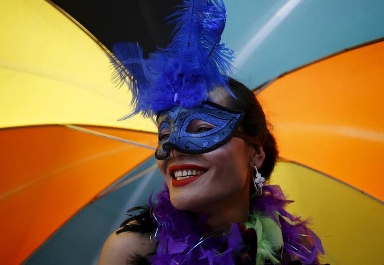 A reveller carrying an umbrella takes part in a LGBT (lesbian, gay, bisexual, and transgender) pride parade to mark Gaijatra Festival, also known as the festival of cows, in Kathmandu, Nepal August 30, 2015. REUTERS/Navesh Chitrakar
