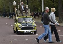 British comedian Rowan Atkinson, in character as 'Mr Bean', rides on a Mini car along The Mall in central London, September 4, 2015. REUTERS/Toby Melville