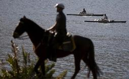 A policeman on a horse patrols as rowers practice at Rodrigo de Freitas Lagoon in Rio de Janeiro August 12, 2015. Rodrigo de Freitas lagoon will host the rowing and canoe sprint competitions in the 2016 Olympic Games. REUTERS/Ricardo Moraes