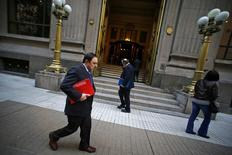 Peatones caminan afuera de la entrada principal del Banco Central de Chile, en el centro de Santiago, 25 de agosto de 2014. Chile registró un inesperado déficit comercial de 62 millones de dólares en agosto, debido a una baja en los envíos liderados por el cobre y una caída menor de las importaciones, dijo el lunes el Banco Central. REUTERS/Ivan Alvarado