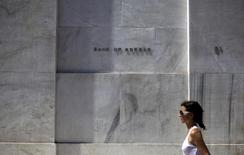 A woman walks past the headquarters of the Bank of Greece in Athens, Greece, August 19, 2015. REUTERS/Stoyan Nenov