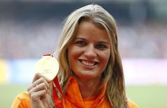 Dafne Schippers of the Netherland presents her gold medal as she poses on the podium after the women's 200m event during the 15th IAAF World Championships at the National Stadium in Beijing, China, August 29, 2015.        REUTERS/Damir Sagolj